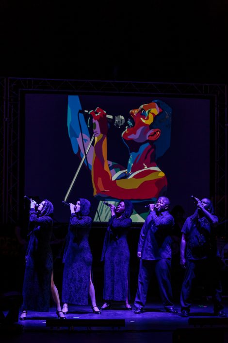 singers performing in front of picture of freddie mercury at decades rewind